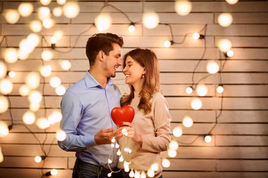 A couple holding a heart symbol and background lighting